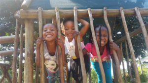 three children on a playground at a pre school in Nelspruit